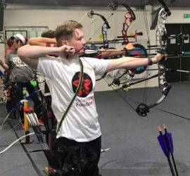 Nathan shooting arrow at archery charity event